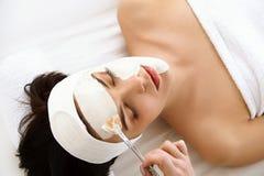 Kuuroordmasker. Vrouw in Kuuroordsalon. Gezichtsmasker. Gezichtsclay mask. Stock Foto