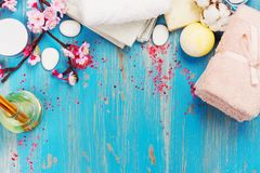 Kuuroordsamenstelling met katoenen handdoeken, aromaolie, overzees zout en stenen op blauwe achtergrond royalty-vrije stock afbeeldingen