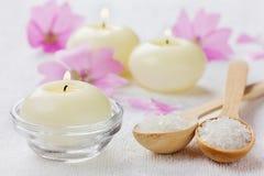 Kuuroordsamenstelling met overzees zout bad in houten lepel, roze bloemen en brandende kaarsen op een witte oppervlakte Royalty-vrije Stock Foto