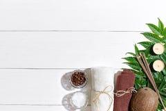 KUUROORDstilleven met handdoek, kaarsen en groene bladeren op een witte houten oppervlakte Stock Foto