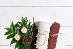 KUUROORDstilleven met handdoek, kaarsen en groene bladeren op een witte houten oppervlakte Royalty-vrije Stock Afbeeldingen
