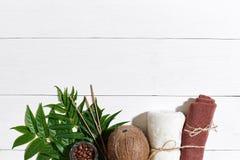 KUUROORDstilleven met handdoek, kaarsen en groene bladeren op een witte houten oppervlakte Stock Foto's