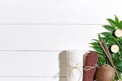 KUUROORDstilleven met handdoek, kaarsen en groene bladeren op een witte houten oppervlakte Stock Fotografie