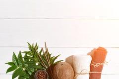 KUUROORDstilleven met handdoek, kaarsen en groene bladeren op een witte houten oppervlakte Zongloed Royalty-vrije Stock Afbeelding