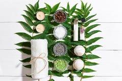 KUUROORDstilleven met handdoek, kaarsen, schrobben de verschillende ingrediënten voor lichaam en groene bladeren op een witte hou Stock Foto's