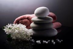 Kuuroordstilleven met stapel stenen, handdoek, overzeese zoute en witte bloemen op donkere achtergrond Stock Fotografie
