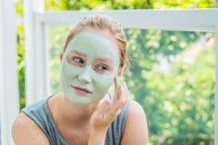 Kuuroordvrouw die Gezichts groen kleimasker toepassen Schoonheidsbehandelingen Cl royalty-vrije stock foto
