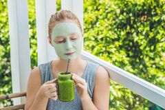 Kuuroordvrouw die Gezichts groen kleimasker toepassen Schoonheidsbehandelingen Verse groene smoothie met banaan en spinazie met h stock foto's