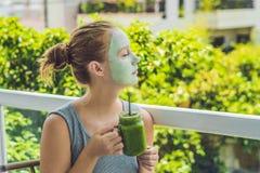 Kuuroordvrouw die Gezichts groen kleimasker toepassen Schoonheidsbehandelingen Verse groene smoothie met banaan en spinazie met h stock fotografie