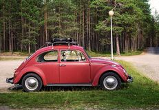 KUUSAMO, FINLAND - AUGUST 15, 2017: Old red car Volkswagen Beetl. E with a black suitcase on the trunk Stock Photography