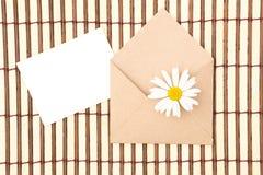 Kuvert av kraft papper med ett tomt meddelande och med det vita podiet arkivfoton