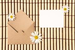 Kuvert av kraft papper med ett tomt meddelande och med det vita podiet arkivbilder