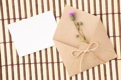 Kuvert av kraft papper med ett tomt meddelande och med härliga blommor arkivbilder