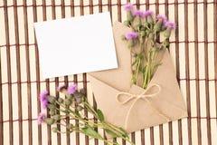 Kuvert av kraft papper med ett tomt meddelande och med härliga blommor fotografering för bildbyråer