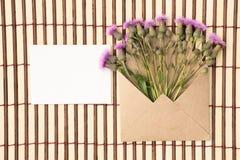 Kuvert av kraft papper med ett tomt meddelande och med härliga blommor arkivfoto