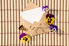 Kuvert av kraft papper med ett tomt meddelande och med härliga blommor royaltyfri foto