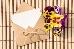 Kuvert av kraft papper med ett tomt meddelande och med härliga blommor arkivfoton