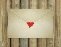 Kuvert för förälskelsebokstav som är bifogat vid en röd hjärta Arkivfoton