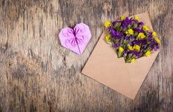 Kuvert med blommor Vildblommor i ett kuvert Hjärta av origami Royaltyfri Bild