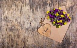 Kuvert med blommor Vildblommor i ett kuvert Hjärta som göras av trä Romantiskt begrepp Royaltyfri Fotografi