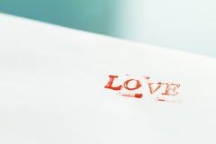 Kuvert med bokstavsFÖRÄLSKELSE på en tabell man för begreppskyssförälskelse till kvinnan Royaltyfria Foton