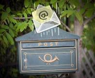 Kuvert med emailtecknet som tappar in i brevlåda Royaltyfri Bild