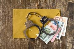 Kuvert med euroräkningar och handbojor Arkivbilder