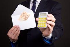 Kuvert med pengar och räknemaskinen i händer för affärsman Arkivbilder