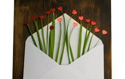Kuvert med röd hjärta och gräs förälskelse för kuverthjärtabokstav valentin för dag s 14th Februari Arkivbild