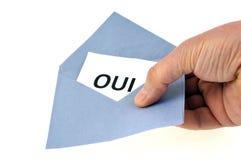 Kuvert som ja rymms i hand p? vit bakgrund med ordet i fransman arkivfoton