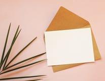Kuvert, vitt tomt papper och en palmblad på en rosa bakgrund fotografering för bildbyråer