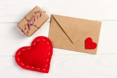 Kuvertpost med den röda hjärta- och gåvaasken över vit träbakgrund Valentine Day Card, förälskelse- eller bröllophälsningbegrepp royaltyfri bild