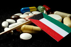 Kuwaiti flag with lot of medical pills isolated on black background Royalty Free Stock Photos