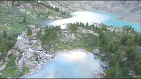 Kuyguk lake and waterfall in Altai mountains. Russian landscape aerial view stock video