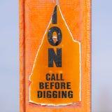 Kvadrera ett sönderrivet varningstecken på en ljus orange stolpe mot en oskarp bakgrund royaltyfri bild