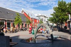 Kvadrera i Reykjavik med en springbrunn och utomhus- kaféer Arkivfoto