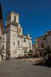 Kvadrera med för byggnader, kyrklig och blå himmel för restauranger, i Nimes Royaltyfria Bilder