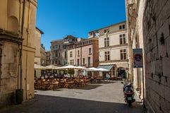 Kvadrera med restauranger, byggnader och blå himmel Nimes Arkivbilder