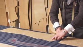 Kvalificerad idérik märkes- man som arbetar i visningslokalen som gör modeller för att sy på textilmaterial stock video