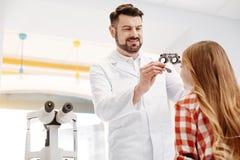 Kvalificerad yrkesmässig optiker som försöker på speciala exponeringsglas Arkivbilder