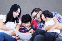 Kvalitets- tid för familj på den röda soffan med touchpaden Royaltyfri Bild