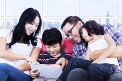 Kvalitets- tid för familj genom att använda touchpaden på lägenheten Arkivbild