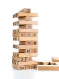 Kvarter av modig jenga på vit bakgrund Vertikalt torn som är helt och i lek Träkvarter i bunt med diagram siffra på Arkivfoton