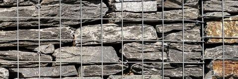 Kvarter för behållande vägg med ingreppstråd stenar korgen Arkivfoto