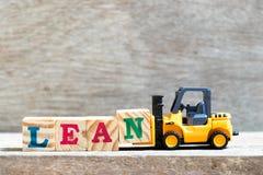 Kvarter n för bokstaven för leksakgaffeltruckhållen till ordet lutar på träbakgrund arkivbilder
