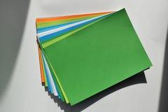 Kvarteret av kulör A4 täcker på en vit bakgrund, grön färg som är upplyst vid solen Arkivfoton