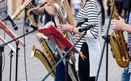 Kvartett av unga musiker som spelar saxofoner under utomhus- performa Arkivfoton