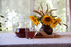 Kvass (kvas) in a transparent jug, bread and a bouquet of sunflo Stock Photography