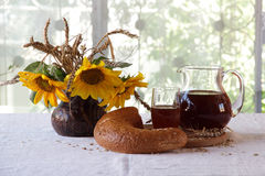 Kvass (kvas) in a transparent jug, rye bread and a bouquet of su Royalty Free Stock Photography