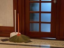 Kvast med det orange handtaget och skopan av vitt pulver som framme lutar av en rengörande utrustning för trädörrgolv arkivbild